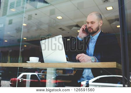 Bearded businessman in luxury suit is calling via mobile phone to client after reading his order in e-mail on portable net-book. Serious CEO is phoning via cell phone during work on laptop computer