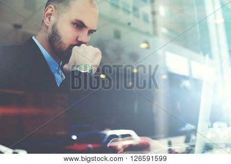 View through the window of a cafe with double exposition of young serious man successful trader is monitoring exchange trading via laptop computer while is sitting in modern coffee shop interior