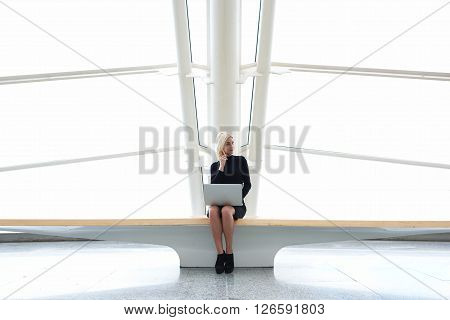 Young woman professional photographer is calling via mobile phone to model which she had found on the network on portable laptop computer to invite her to shooting while is sitting in modern interior