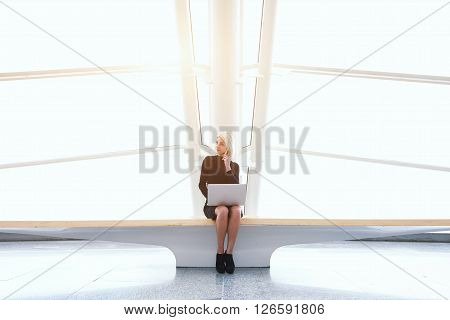 Skilled businesswoman with net-book on knee is phoning via mobile phone while is sitting in co-working space. Modern female is using laptop computer and cell telephone to preparing for conference