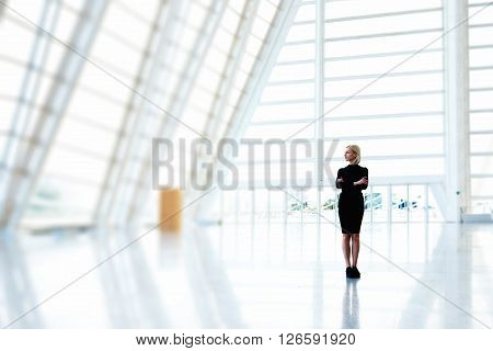 Young female property buyer is thinking of buying a modern skyscraper premises for future office space. Woman entrepreneur is standing with crossed arms in empty interior with copy space for advertise