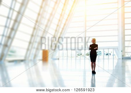 Young beautiful woman owner of successful model agency dressed in elegant black dress is standing in modern interior with copy space background for your advertising text message or promotional content