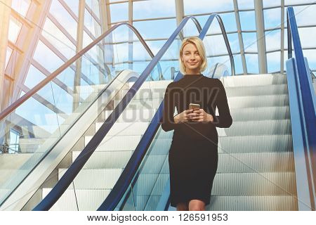 Young female CEO with mobile phone in hands is using moving staircase in modern interior for change the floor in skyscraper office. Businesswoman with cell telephone in hands is looking at camera