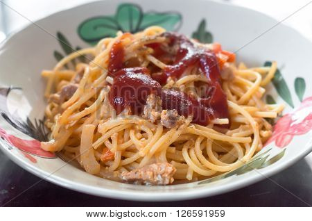 Fried spaghetti and pork with tomato sauce in plate