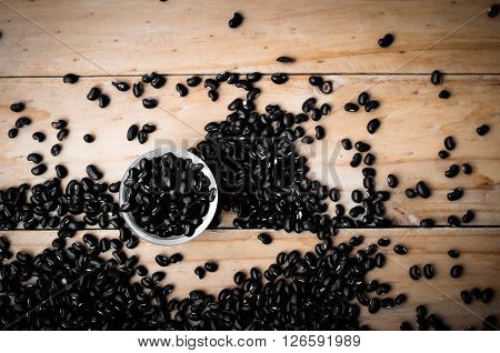 black bean seed on wooden rustic background in warm tone.