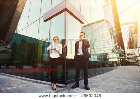 Man lawyer is having mobile phone conversation while his client is checking time before start court session. Male entrepreneur is calling with cell telephone while is standing with partner outside