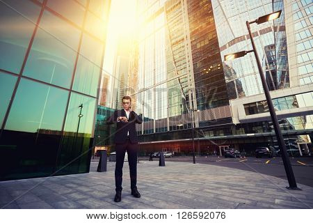 Skilled man managing director of prosperous company is checking time and talking on mobile phone while is standing outside near skyscrapers. Successful male CEO having cell telephone conversation