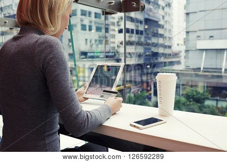 Woman is using credit card and touch pad for o-nline booking ticket on plane to return from business trip from China. Female is making shopping in internet via digital tablet while is sitting in cafe