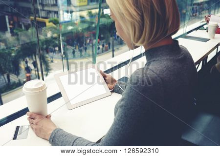Woman is transferring of funds from credit card via touch pad app while is sitting in business center. Young hipster girl is booking hotel via portable digital tablet with copy space on the screen