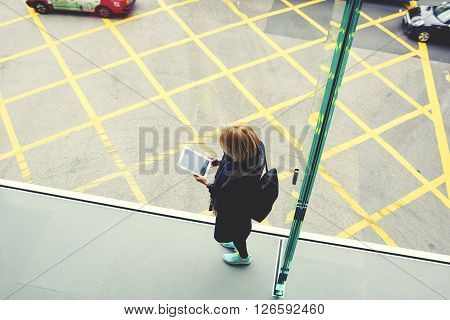 Top view of a woman traveler with a rucksack on her back is holding touch pad with blank copy space screen for your content. Young hipster girl is reading information in network on digital tablet