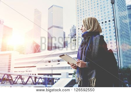 Young beautiful woman with portable touch pad in hands is enjoying view of Hong Kong business center outside the window background with copy space for advertising text message or promotional content