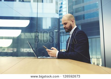Intelligent businessman is reading text message on mobile phone while is sitting with net-book in office interior. Young male entrepreneur is searching on web site information via cell telephone