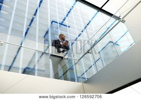 View from below of a young economist of a successful company is waiting for a call on mobile phone while is standing in skyscraper office interior with modern design. Copy space for your text message