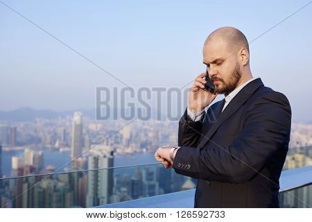 Intelligent man jurist is checking time and calling via cellphone to client which he expects while is standing on a tall skyscraper against developed Hong Kong city with copy space for your content