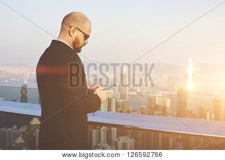 Man proud owner of big business is searching information on web page via cell telephone while is standing on a building roof against view of Hong Kong city with copy space background for your content