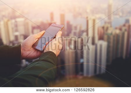 Closeup of man`s hands is holding smart phone with copy space screen for your advertising text message. Closely of male manager is watching wold news o-nline via cell telephone during work break