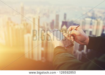Closeup of man economist is typing something on mobile phone touch screen with copy space by using stylus. Closely of successful businessman is using cell telephone before meeting with client