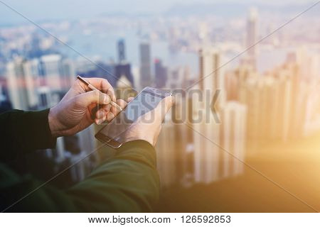 Closely of businessman is writing stylus on touchscreen of mobile phone against blurred Hong Kong city. Closeup of male CEO is searching information on web page via cell telephone during work break
