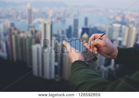 Closely of a businessman is making a work plan on mobile phone by using stylus while is standing on roof against Hong Kong city. Male entrepreneur is holding cell telephone with copy space screen