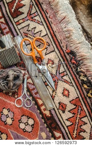 Restoration of of worn edge of the old wool carpet handmade