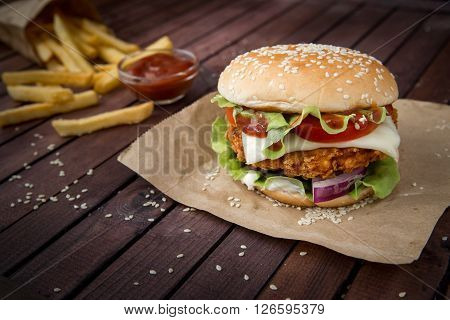 Closeup of home made burgers on sesame buns with beef patties and fresh salad ingredients on wooden background