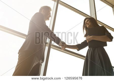 Business men and women shaking hands with a smile on the background of the large panoramic windows in a modern business center. Models dressed in a dark business suits.