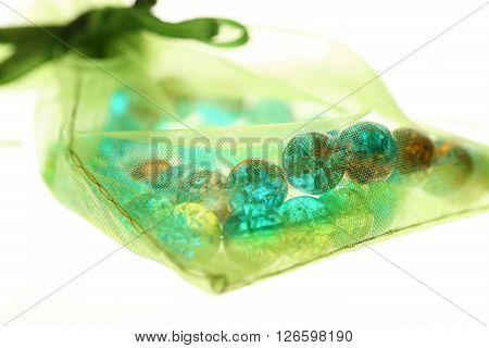 Glass bracelet in decorative transparent bag on white isolated background