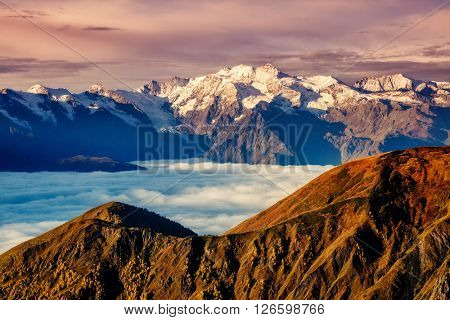Fantastic panorama range shrouded in mist at the foot of Mt. Ushba. Dramatic foggy scene. Location famous place Upper Svaneti, Mestia, Georgia, Europe. High Caucasus ridge. Warm toning, Beauty world.
