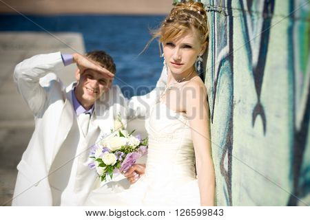 Newly married caucasian couple standing near stone wall