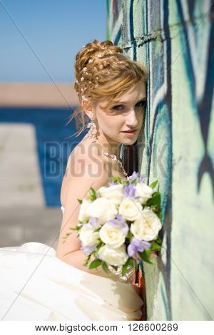 Beautiful bride with bouquet near wall with grafity