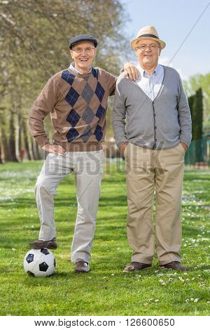 Full length portrait of two senior gentlemen posing in a park with a football on a sunny day