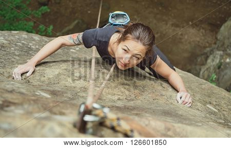 Beautiful young woman in safety equipment climbing on stone rock and looking at camera top view