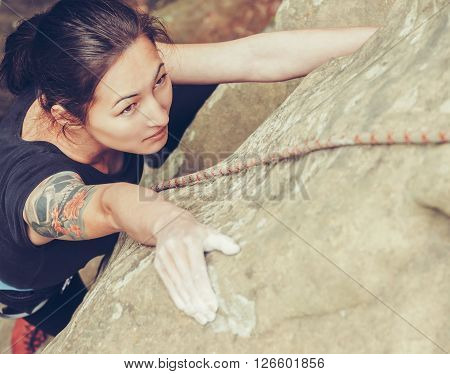 Sporty young woman wearing in safety harness with rope climbing on rock outdoor in summer top view