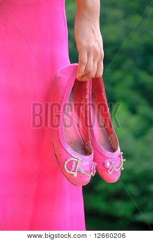 Hand Of A Young Girl Holding A Pair Of Shoes