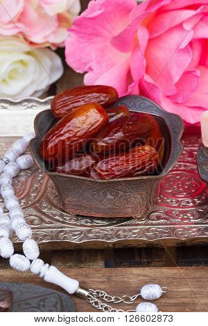 Date fruit with rosemary in copper vase on oriental traditional tray