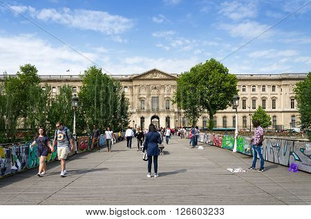 Paris France - May 13 2015: People visit the Pont des Arts or Passerelle des Arts bridge across river Seine in Paris France. on May 13 2015.
