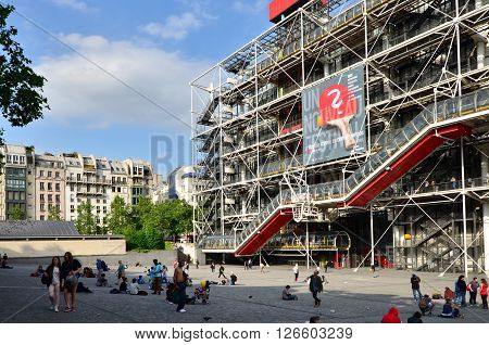 Paris France - May 14 2015: People relaxing at public space in front of Centre of Georges Pompidou on May 14 2015 in Paris France. The Centre of Georges Pompidou is one of the most famous museums of the modern art in the world.