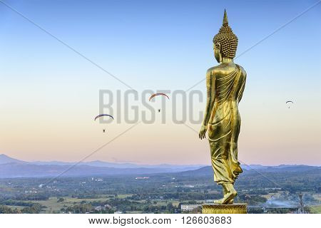the standing Buddha statue in Nan provinceThailand with the para-motor player at the evening