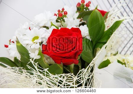 Single red rose. Red rose in the bouquet. A festive bouquet of flowers with a single rose. Romantic gift.