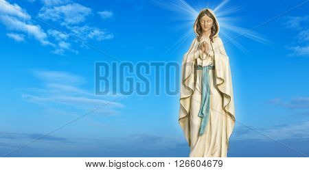 Statue of the Virgin Mary over blue sky background