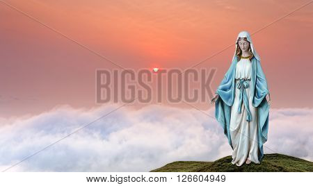 Statue of the Virgin Mary over heavenly sky concept of religion
