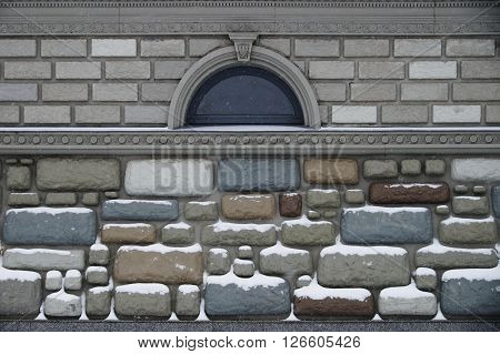 the wall with small window, decorative imitation rubble and bricks
