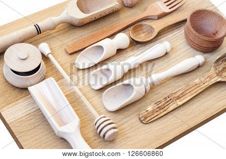 Set of the wooden kitchen utensils on wooden background. spoon mortar kitchen spatula rolling pin bowl fork. Overhead view of wood utensils on wood board isolated on white background.