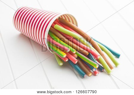 Sweet gummy sticks with different flavor. Tasty candies in paper cup.