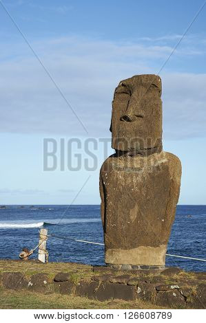 Weathered Moai statue on the coast of Rapa Nui (Easter Island) in the capital Hanga Roa.
