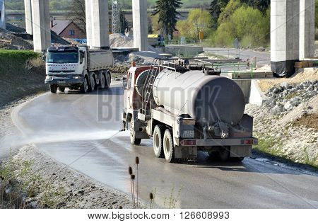 Dolny Hricov Slovakia - April 13 2016: Water tanker splashes water on the road to prevent dust on work site. There is slovak highway labeled