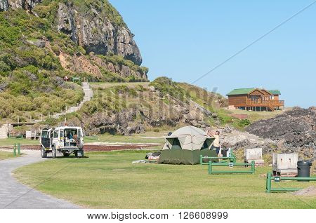 STORMS RIVER MOUTH SOUTH AFRICA - FEBRUARY 28 2016: Tourists erecting a tent with chalets in the back at the rest camp at Storms River Mouth