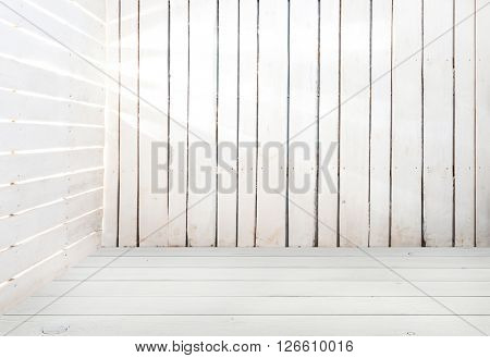 empty white wooden room with light in slits between planks
