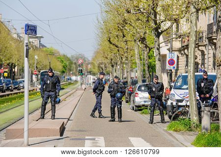 STRASBOURG FRANCE - APR 20 2016: Armed police offiers protectin street as hundreds of people demonstrate as part of nationwide day of protest against proposed labor reforms by Socialist Government