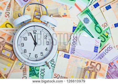 Old Alarm clock and euro paper currency